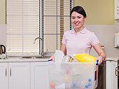 Mixed Race woman carrying recycling bin