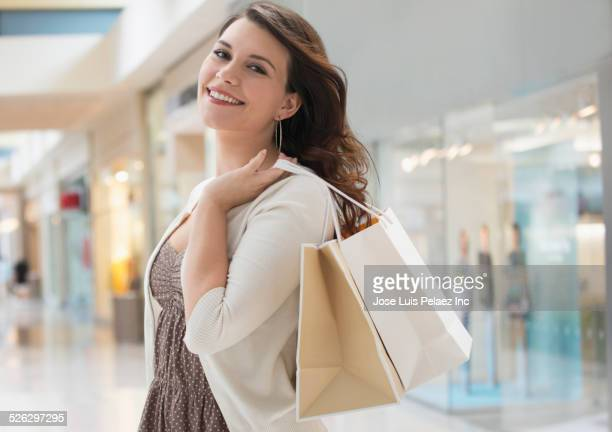 Mixed race woman carrying shopping bag in mall