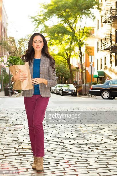 Mixed race woman carrying shopping bag on urban street