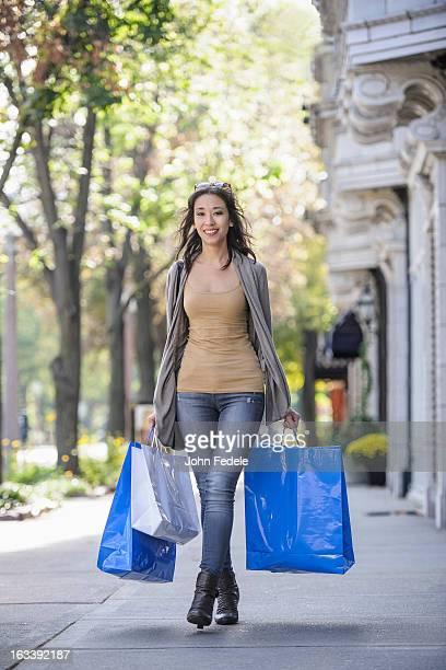 Mixed race woman carrying shopping bags