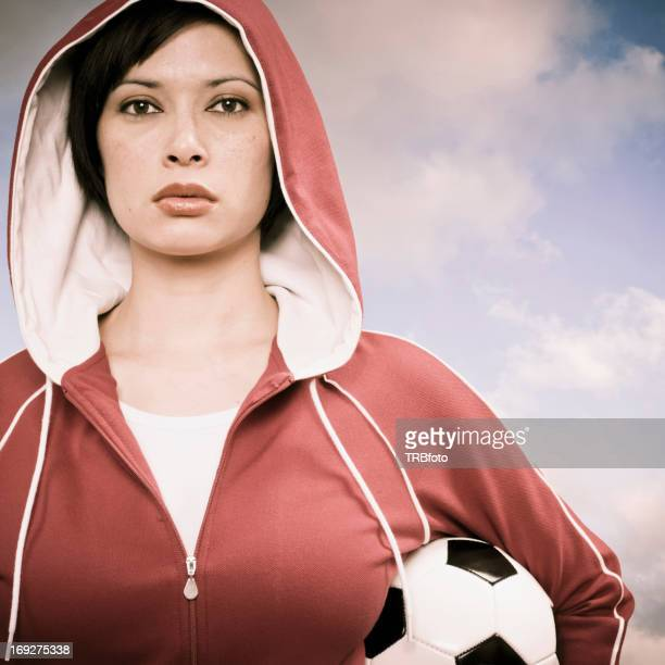 Mixed race woman carrying soccer ball