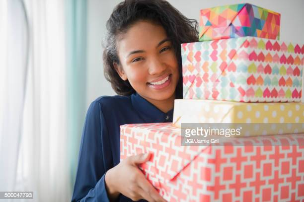 Mixed race woman carrying stack of gifts