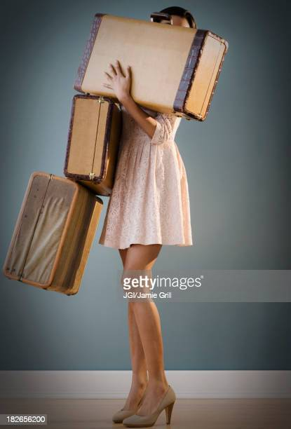 Mixed race woman carrying suitcases