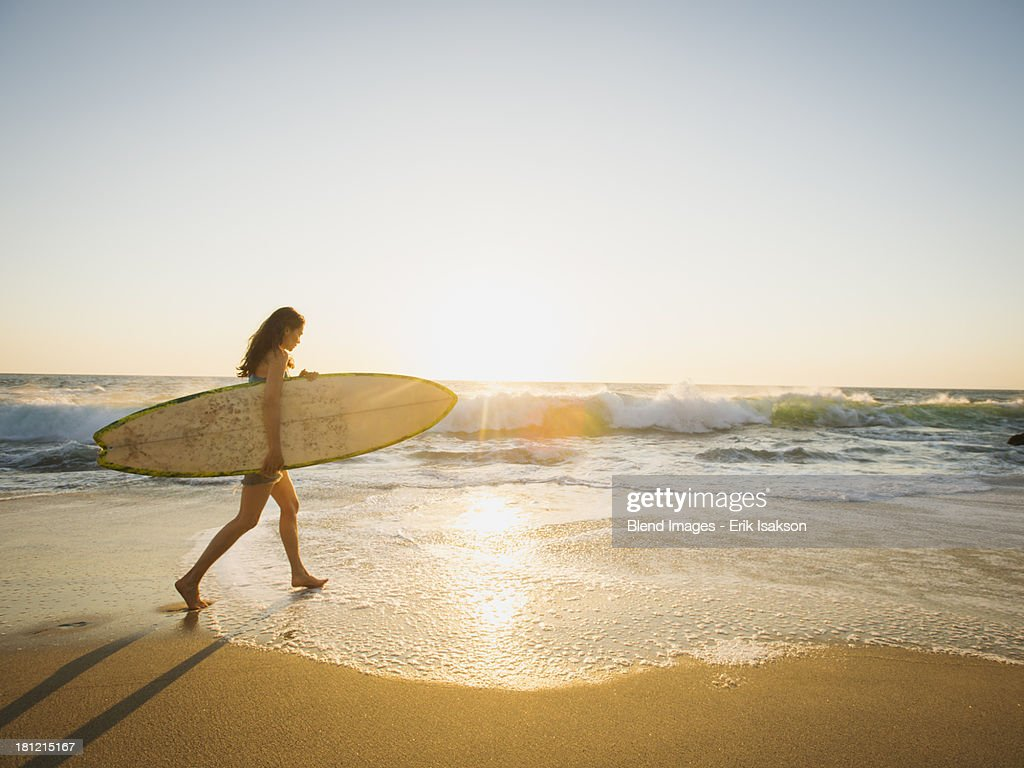 Mixed race woman carrying surfboard on beach : Stock Photo