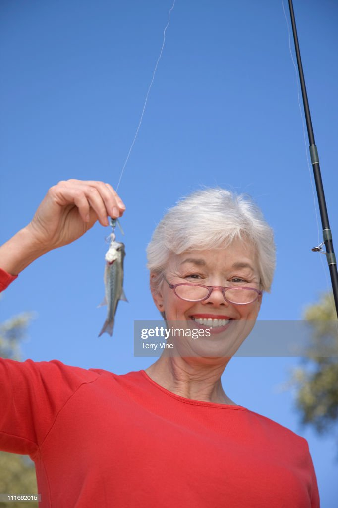 Mixed race woman catching small fish : Stock Photo