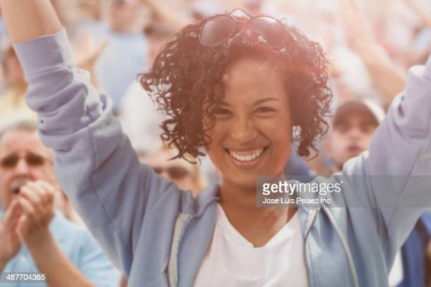 Mixed race woman cheering at sporting event