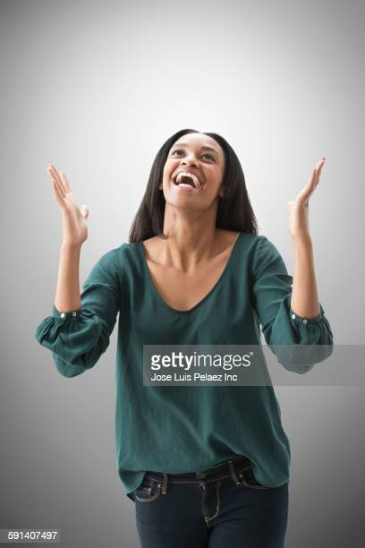 Mixed race woman cheering with arms outstretched