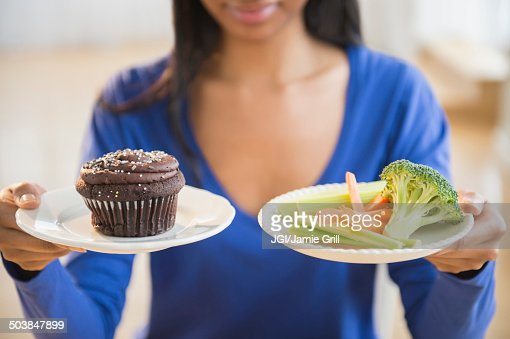 Mixed race woman choosing vegetables or cupcake : Stock Photo