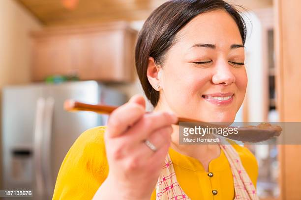 Mixed race woman cooking in kitchen
