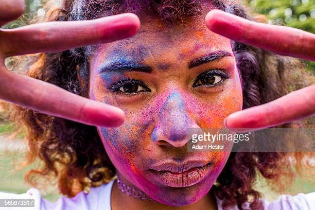 Mixed race woman covered in pigment powder gesturing peace signs