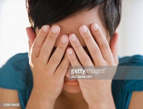 Mixed race woman covering face with hands
