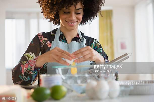 Mixed race woman cracking egg