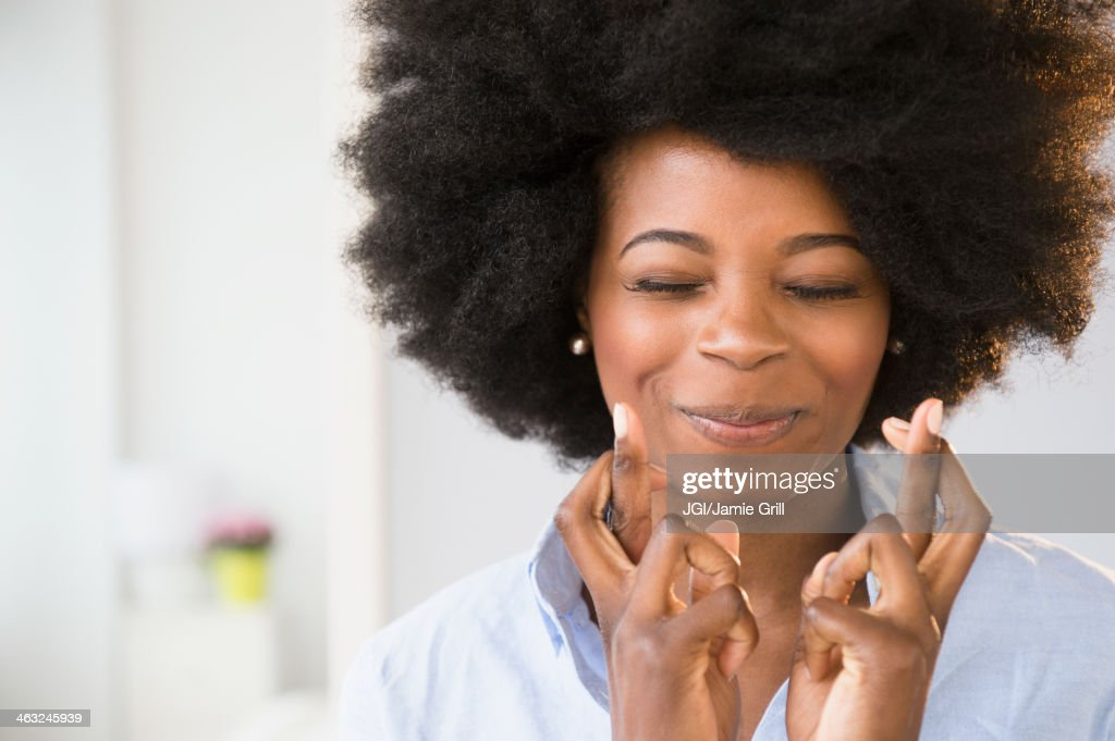 Mixed race woman crossing her fingers : Stock Photo
