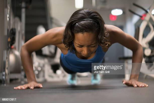 Mixed Race woman doing push-up on floor at gymnasium