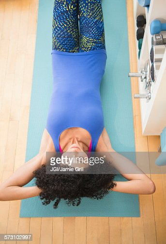 Mixed race woman doing sit-ups in gym