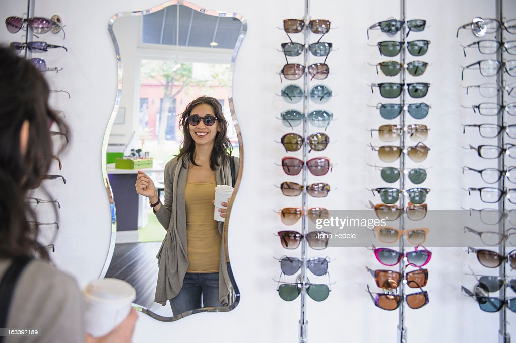Mixed race woman drinking coffee and looking at eyeglasses in shop : Stock Photo