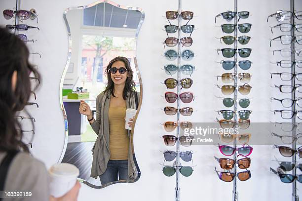 Mixed race woman drinking coffee and looking at eyeglasses in shop