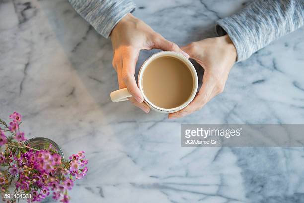 Mixed race woman drinking cup of coffee at table