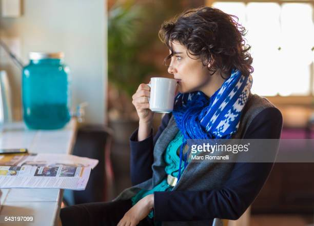 Mixed race woman drinking cup of coffee in cafe