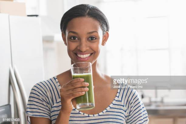 Mixed race woman drinking glass of green juice in kitchen