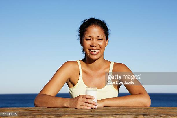 Mixed Race woman drinking milk