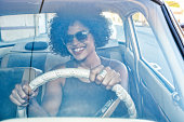 Mixed race woman driving vintage car