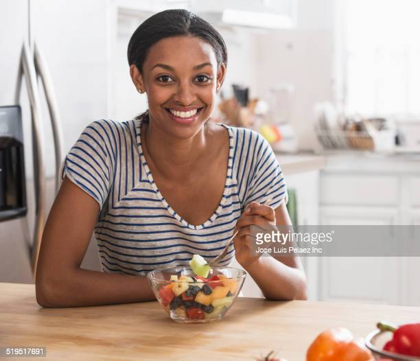 Mixed race woman eating fruit salad in kitchen