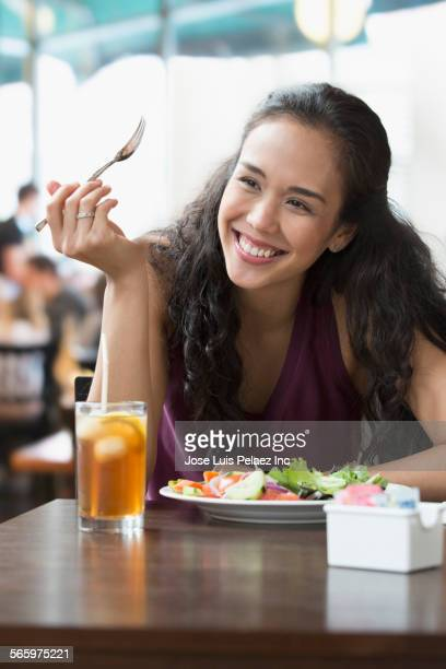 Mixed race woman eating lunch in cafe
