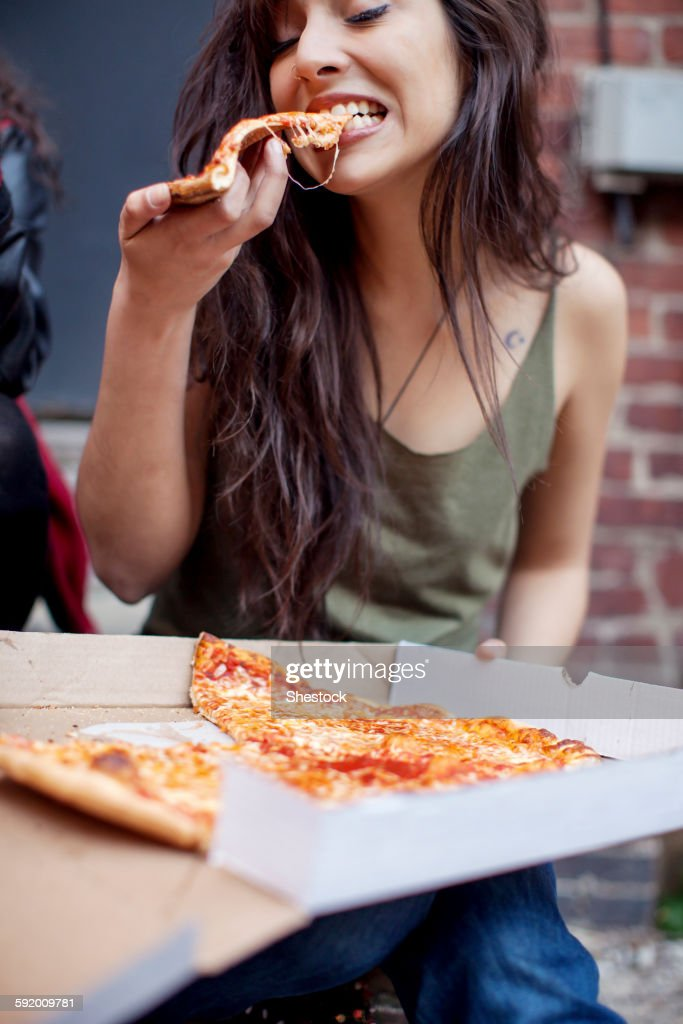 Mixed race woman eating pizza