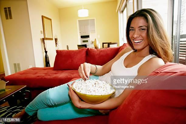 Mixed race woman eating popcorn on sofa