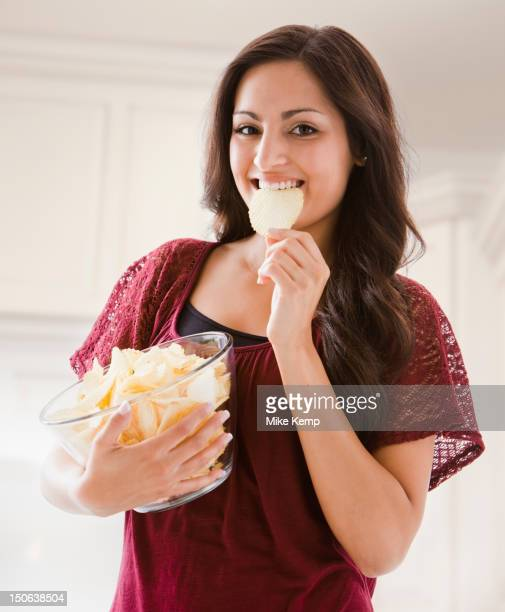 Mixed race woman eating potato chips