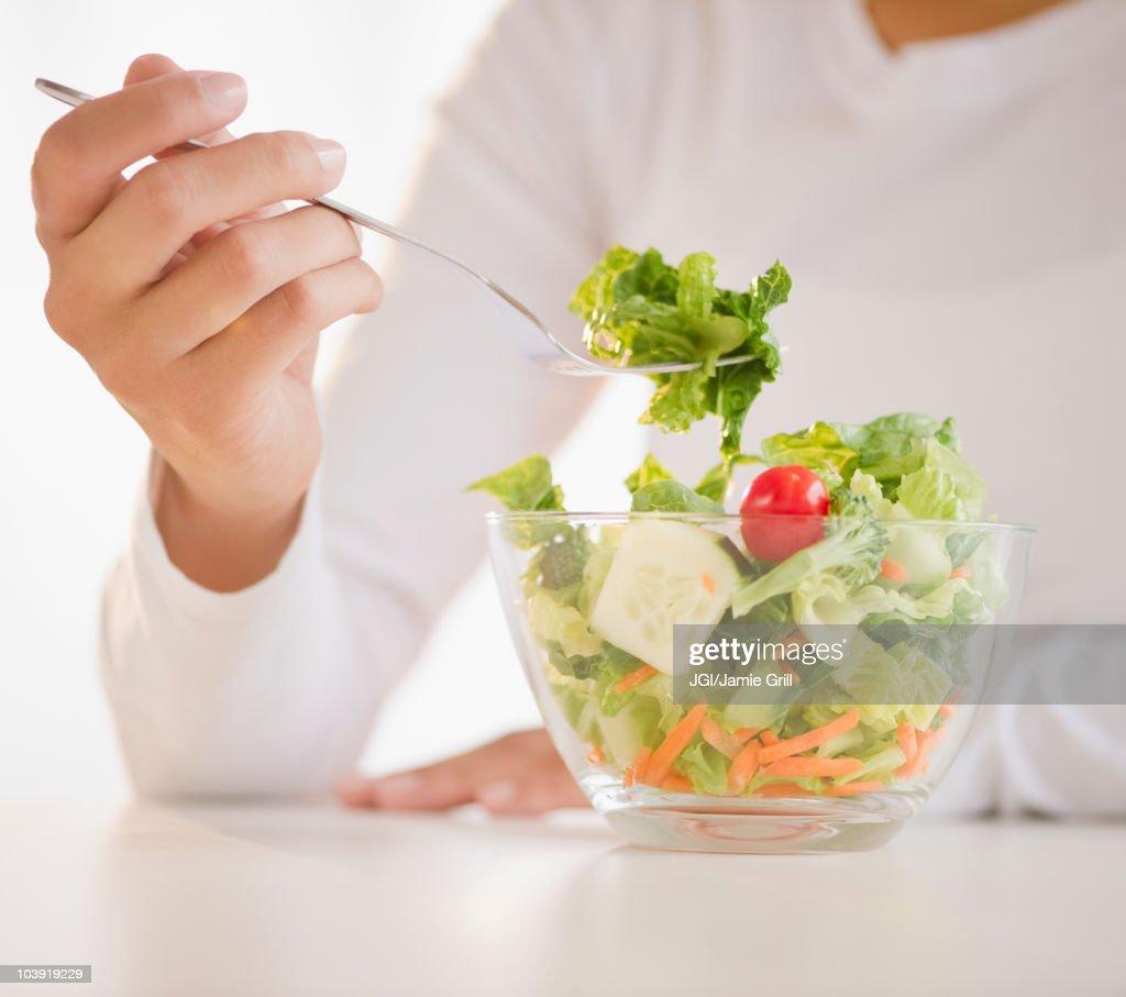 Mixed race woman eating salad : Stock Photo