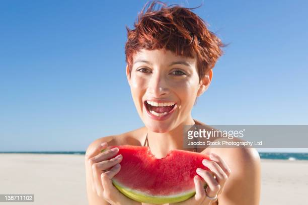 Mixed race woman eating watermelon on beach