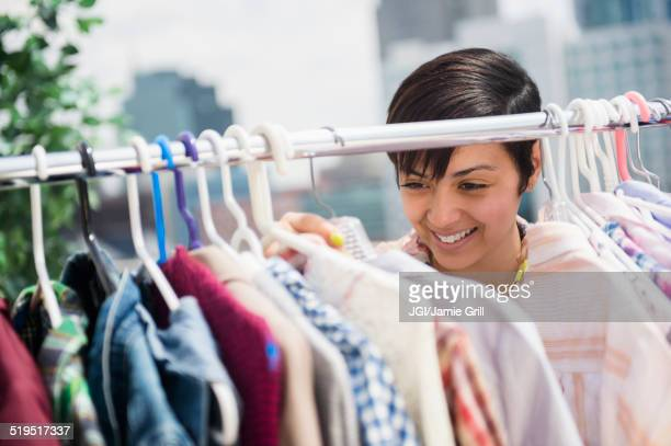 Mixed race woman examining clothing on rack