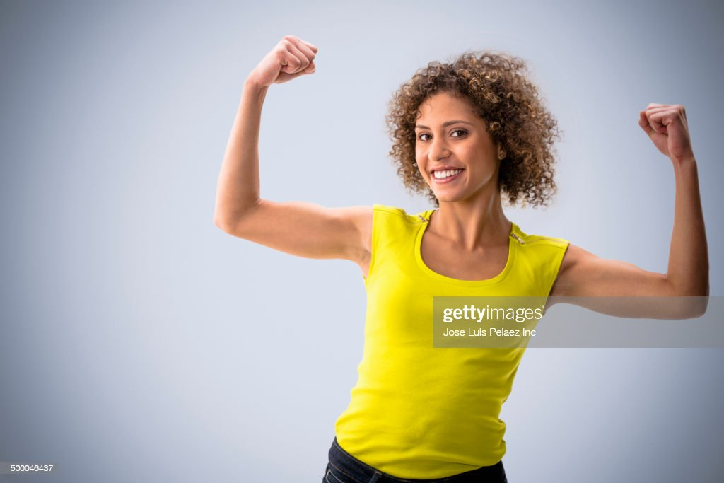 Mixed race woman flexing her muscles