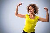 Mixed race woman flexing her muscles