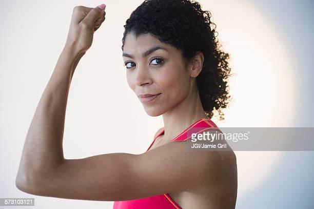 Mixed race woman flexing muscles