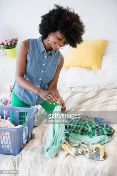 Mixed race woman folding laundry