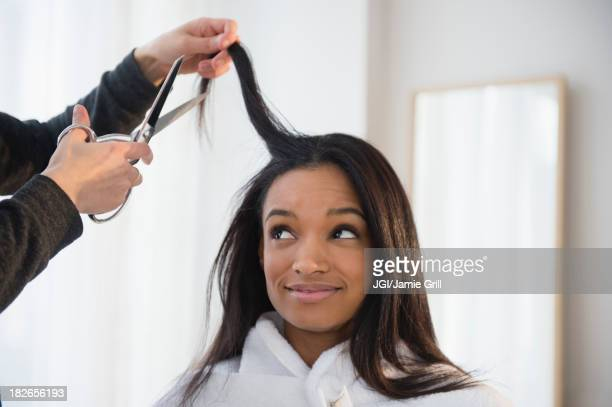 Mixed race woman getting hair cut