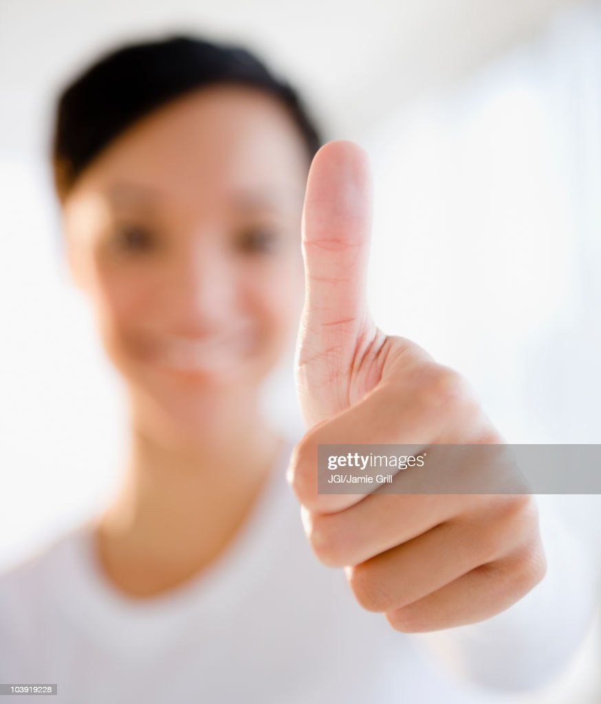 Mixed race woman giving thumbs up sign : Stock Photo
