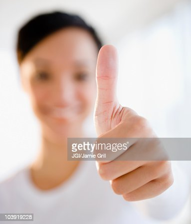 Mixed race woman giving thumbs up sign : Foto de stock