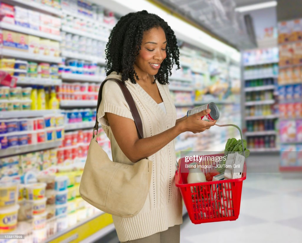Mixed race woman grocery shopping : Stock Photo