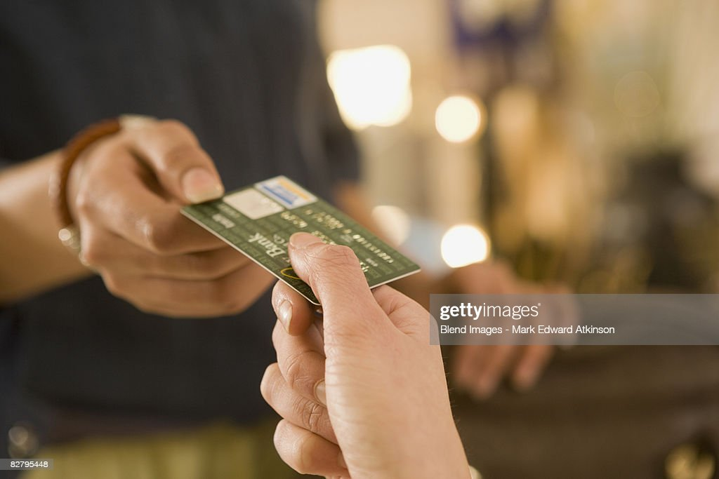 Mixed race woman handing credit card to cashier : Stock Photo