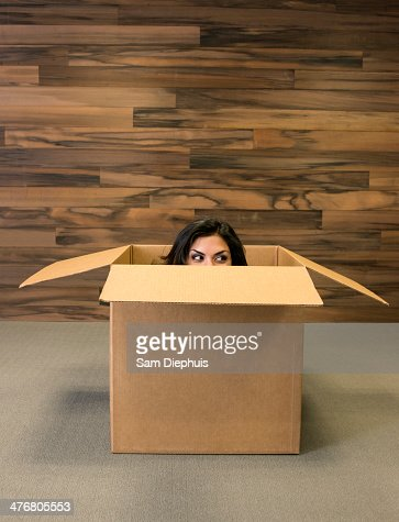 Mixed race woman hiding in cardboard box