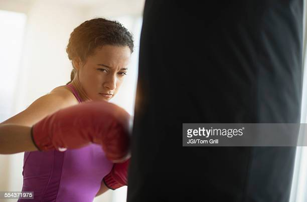 Mixed race woman hitting punching bag in gym