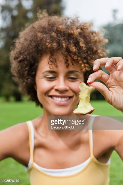 Mixed race woman holding apple core