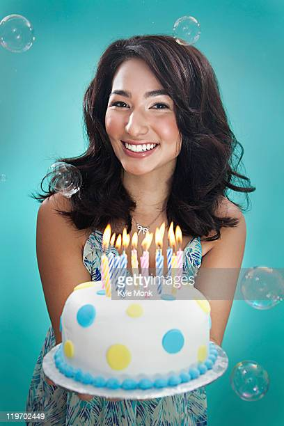 Mixed race woman holding birthday cake