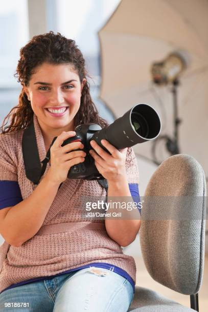Mixed race woman holding camera