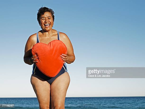 Mixed Race woman holding heart pillow at beach