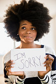 Mixed race woman holding ''I'm sorry'' sign